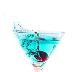 une cerise tombant dans un verre de cocktail