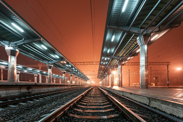 Fotobehang Treinstation Railway station at night. Train platform in fog. Railroad