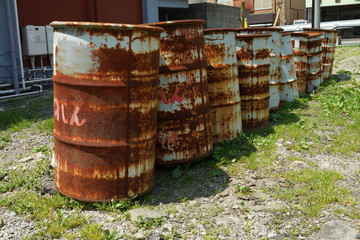 oil drums stacked together in a yard,