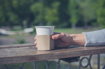 Female hand holding paper cup