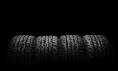 four automobile rubber tires isolated on black background Wall mural