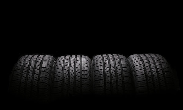 four automobile rubber tires isolated on black background
