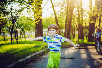Happiness child running on the park on sunset rays.