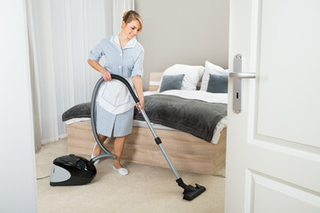 Maid With Vacuum Cleaner In Hotel Room