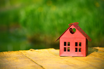 red model of house as symbol on natural green background