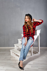 The girl in a hat, plaid shirt and jeans