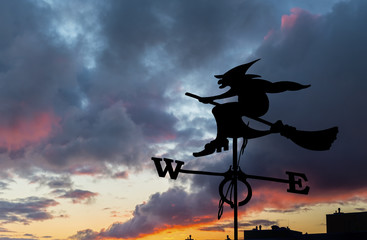 Silhouette of Halloween witch flying on broomstick above a city