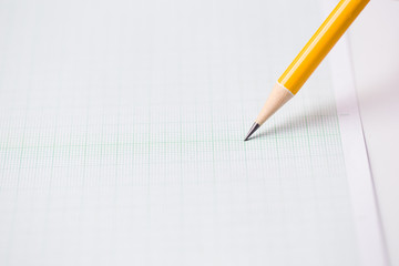 close-up yellow pencil on graph paper background