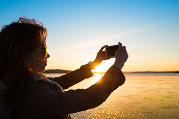 Woman taking selfie on a beach during sunset