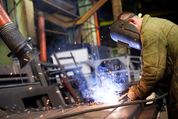 Factory welder worker during gas metal arc welding works