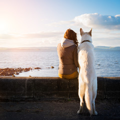 Young hipster girl with her pet dog at a seaside