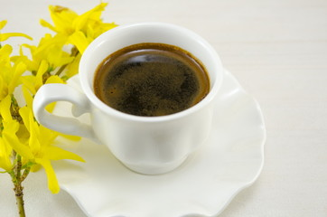 White cup of coffee on a table decorated with flowers
