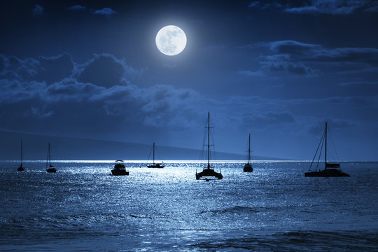 Moonlit nighttime sky over a calm ocean scene in Maui Hawaii