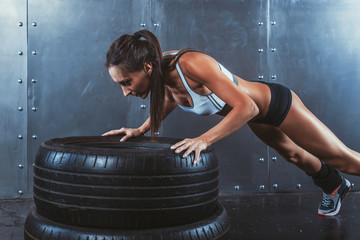 Wall Mural - Sportswoman. Fit sporty woman doing push ups on tire strength
