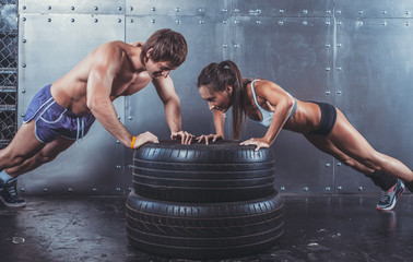 Wall Mural - Sportsmen. Fit sporty woman and man doing push ups on tire