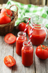 Fresh red tomatos in basket and juice in bottles
