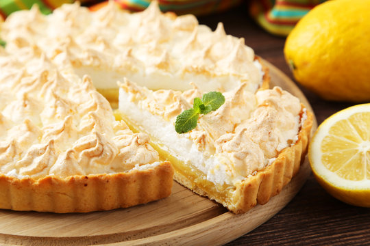 Lemon meringue pie on cutting board on wooden background