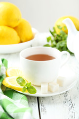 Cup of tea with mint and lemon on white wooden background