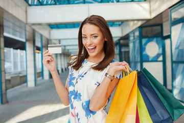 Happy young woman with shopping bags holding a credit card