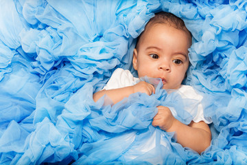 Chubby African small baby laying on the blue cloth