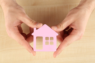 Female hands holding house on wooden background