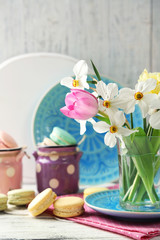 Spring bouquet in glass mug  and tasty macaroons on color wooden background