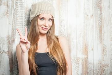 Cheerful hipster woman is wishing peace everyone