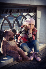 sad girl in a pink beret sits on a parapet with big toy a bear.