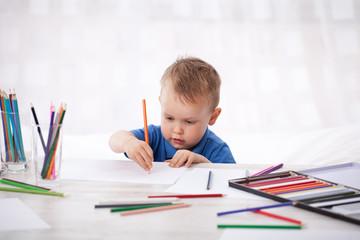 Kleiner Junge malt Bilder mit Buntstiften