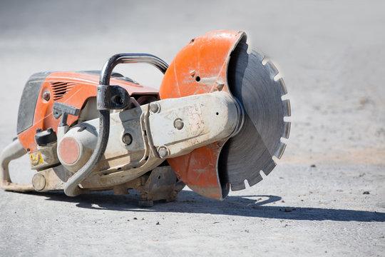 Concrete gasoline saw grinder at construction site