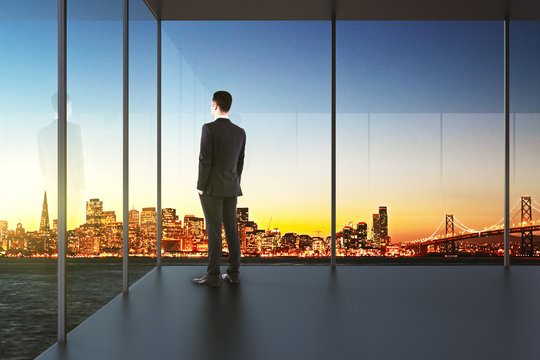 businessman in the office looking over the city at sunset