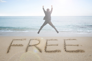 Jumping businessman cheering with free word handwritten in sand