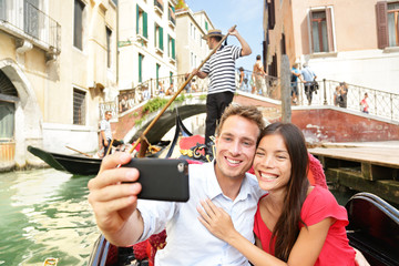 Selfie couple taking picture in Venice gondola