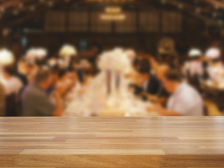 Empty wooden table and blurred dinning people background