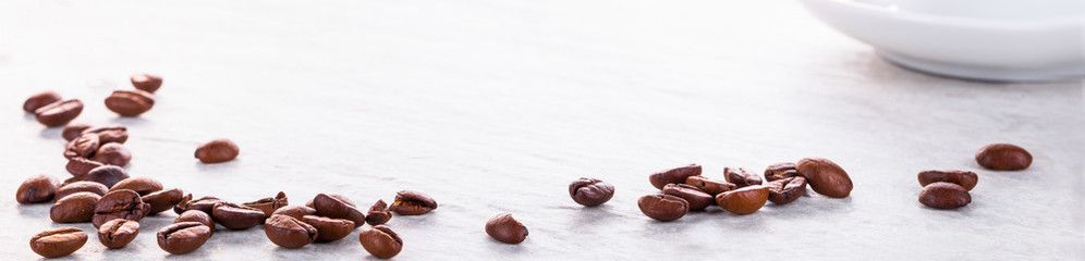 Kaffeebohnen und Kaffeetasse auf Steinplatte