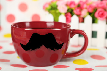 Red cup with paper mustache on colorful background