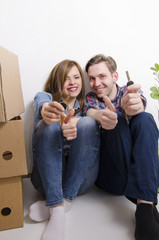 Young happy couple, moving in, holding keys and thumbs up