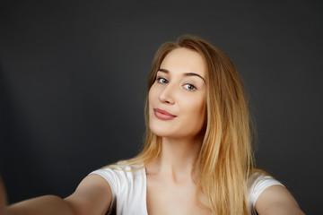 young pretty blonde women taking selfie on cell phone