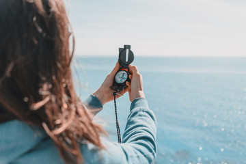 Traveler woman with a compass on coastline