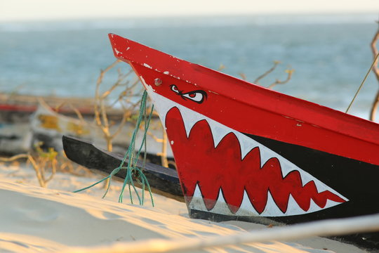Innocent painting on a pirogue prow