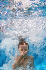 Swimming child jumps underwater in the blue pool with splashes