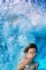 Funny face portrait of smiling child swimming underwater in pool