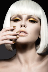 Beautiful girl in a white wig, with gold makeup and nails