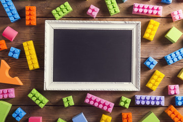 Picture frame and colorful blocks laid on wooden background.