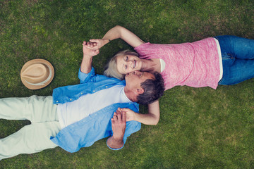 Beautiful seniors lying on a grass in a park hugging