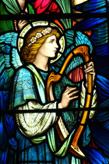 Fototapete - Angel making music on a harp (stained glass)