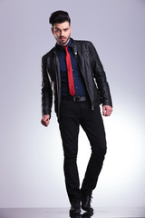 young business man standing on grey studio background.