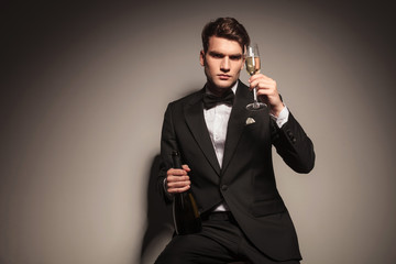 business man holding a bottle and a glass of champagne.