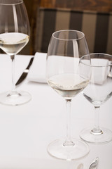 Restaurant dinner table with glass of wine