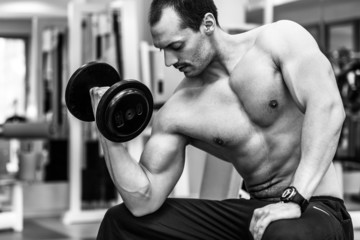 Muscular male bodybuilder sitting and training with dumbbells